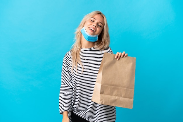 Young russian woman holding a grocery shopping bag isolated on blue laughing