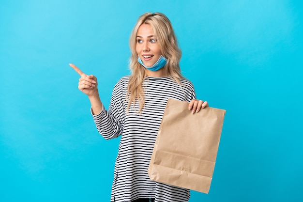 Young russian woman holding a grocery shopping bag isolated on blue pointing finger to the side and presenting a product