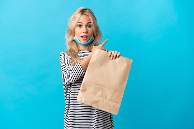 Young russian woman holding a grocery shopping bag isolated on blue surprised and pointing side