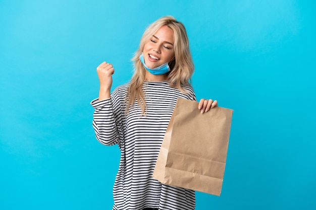 Young russian woman holding a grocery shopping bag isolated on blue wall celebrating a victory