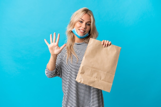 Young russian woman holding a grocery shopping bag isolated on blue wall counting five with fingers