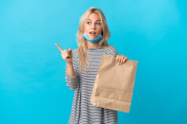 Young russian woman holding a grocery shopping bag isolated on blue wall intending to realizes the solution while lifting a finger up
