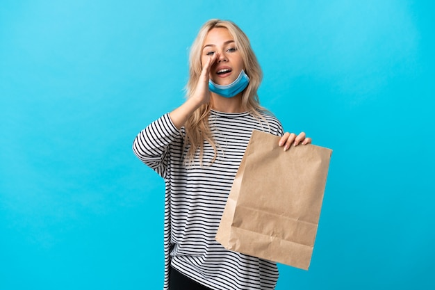 Young russian woman holding a grocery shopping bag isolated on blue wall shouting and announcing something