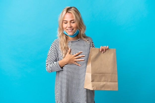 Young russian woman holding a grocery shopping bag isolated on blue wall smiling a lot
