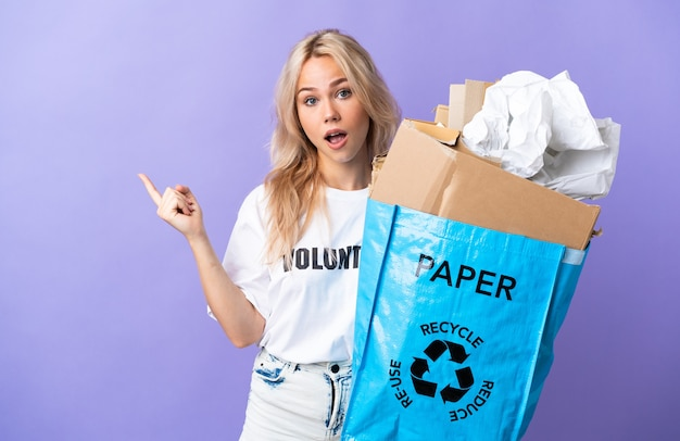 Young russian woman holding a recycling bag full of paper to recycle isolated on purple wall surprised and pointing side