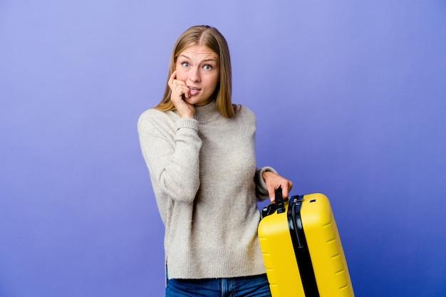神経質で非常に不安な、噛む爪を旅行するためにスーツケースを持っている若いロシア人女性。