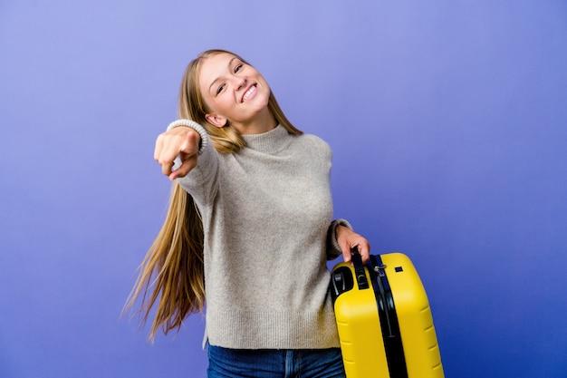 Молодая русская женщина, держащая чемодан для путешествия, веселые улыбки, указывающие на фронт.