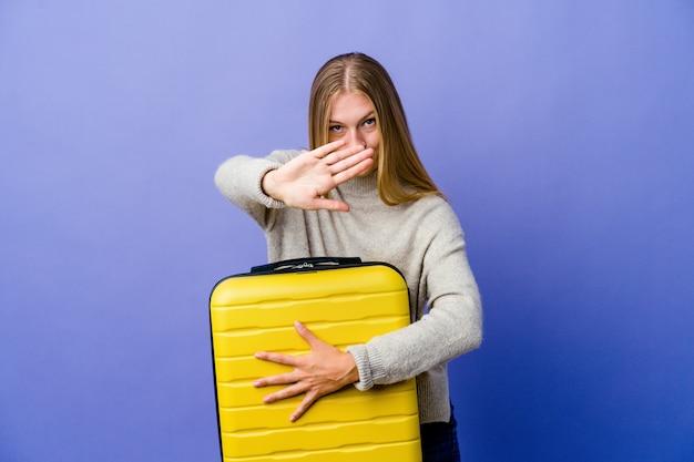拒否ジェスチャーをして旅行するためにスーツケースを持っている若いロシアの女性