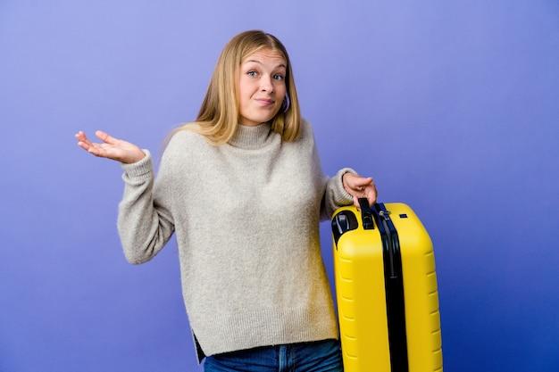Молодая русская женщина, держащая чемодан для путешествия, сомневаясь и пожимая плечами в вопросительном жесте.