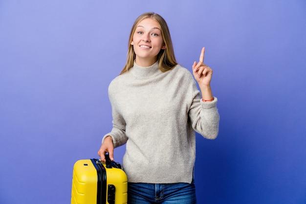 여행 가방을 들고 젊은 러시아 여자는 빈 공간을 보여주는 두 앞 손가락으로 나타냅니다.