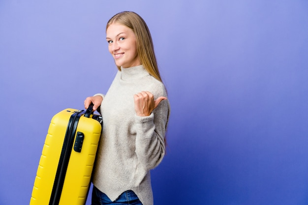 Молодая русская женщина держит чемодан, чтобы путешествовать, глядя далеко, держа руку на лбу