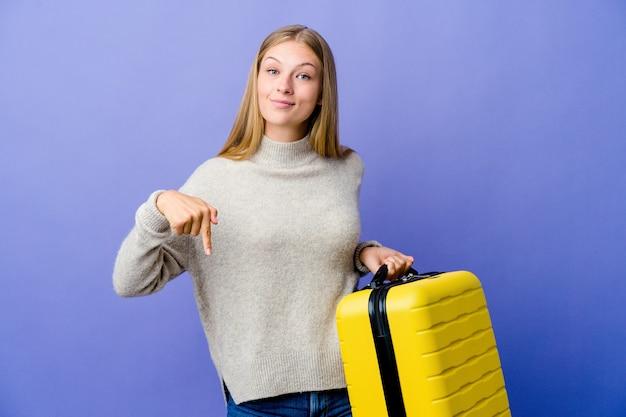 スーツケースを持って旅行する若いロシア人女性が指でポイントを下に向け、前向きな気持ち。