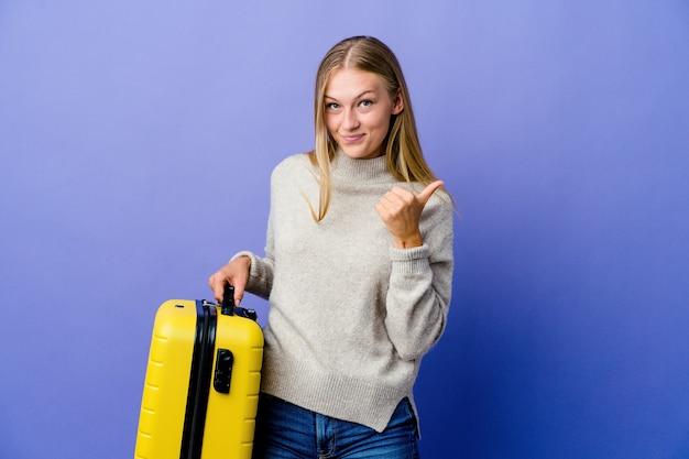 Молодая русская женщина держит чемодан для путешествия, поднимает пальцы вверх, улыбается и уверенно