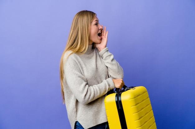 スーツケースを持って叫び、開いた口の近くで手のひらを持って旅行する若いロシア人女性。
