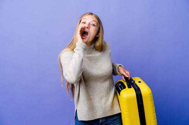 Молодая русская женщина, держащая чемодан для путешествий, кричит, возбуждена вперед.
