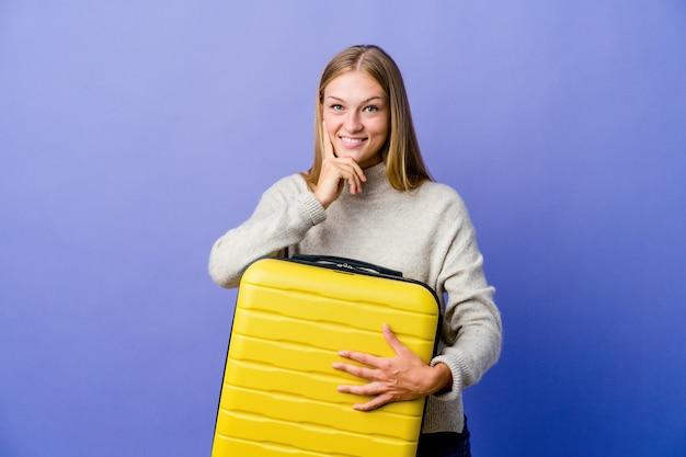 Молодая русская женщина, держащая чемодан для путешествия, улыбается, счастлива и уверенно, трогательно подбородок рукой.