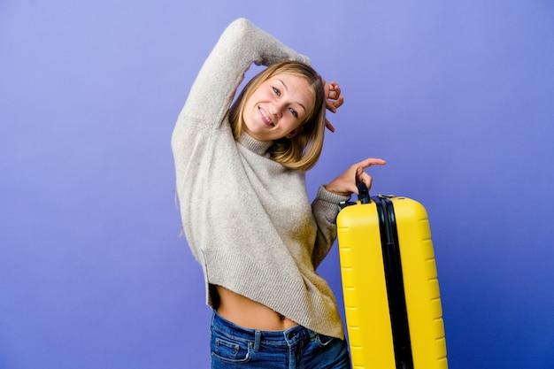 Молодая русская женщина держит чемодан для путешествия, протягивая руки, расслабленное положение.