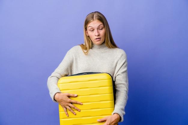 Молодая русская женщина держит чемодан, чтобы путешествовать, уставшая от повторяющейся задачи