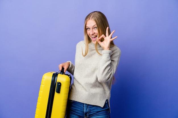 旅行のためにスーツケースを持っている若いロシアの女性は目をまばたきし、手で大丈夫なジェスチャーを保持します。