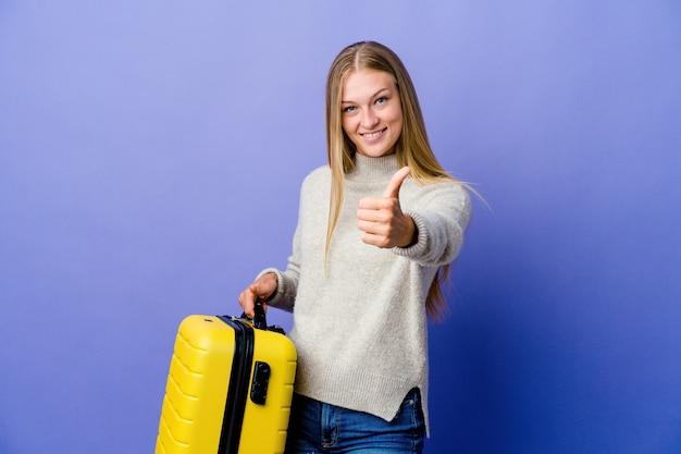 Молодая русская женщина держит чемодан для путешествия с большими пальцами руки вверх, приветствует что-то, поддерживает и уважает концепцию.