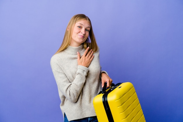 Young russian woman holding suitcase to travel has friendly expression, pressing palm to chest. love concept.