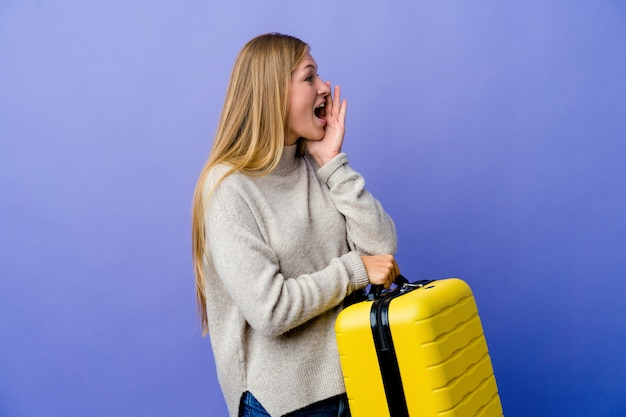 Young russian woman holding suitcase to travel shouting and holding palm near opened mouth.