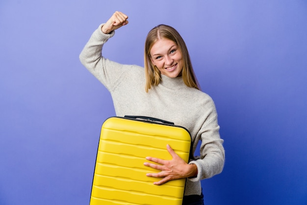 Young russian woman holding suitcase to travel showing strength gesture with arms, symbol of feminine power