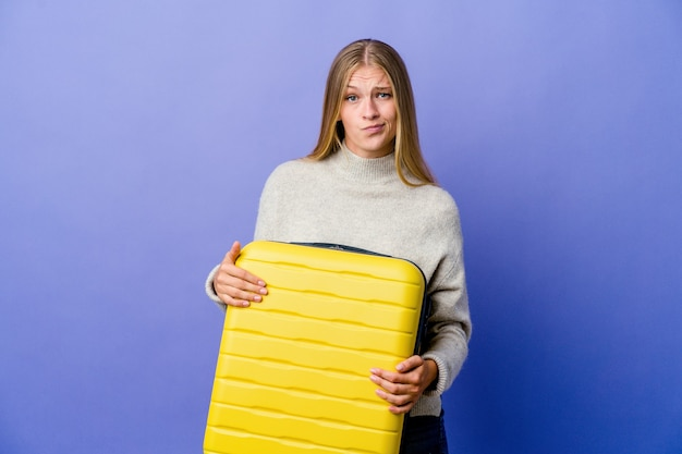Young russian woman holding suitcase to travel unhappy looking in camera with sarcastic expression
