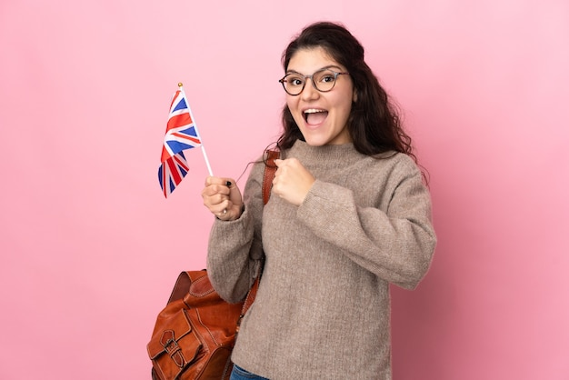 Young russian woman holding an united kingdom flag isolated on pink background celebrating a victory