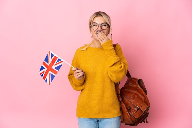 Young russian woman holding an united kingdom flag isolated on pink background happy and smiling covering mouth with hand