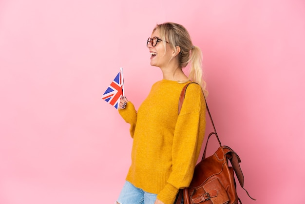 Young russian woman holding an united kingdom flag isolated on pink background laughing in lateral position