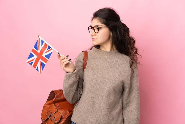 Young russian woman holding an united kingdom flag isolated on pink background looking to the side
