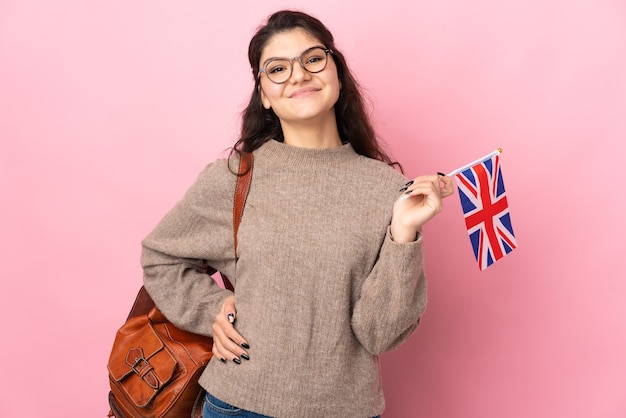 Young russian woman holding an united kingdom flag isolated on pink background posing with arms at hip and smiling