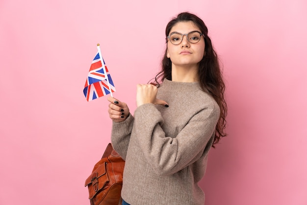 Young russian woman holding an united kingdom flag isolated on pink background proud and self-satisfied