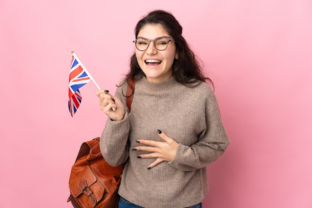 Young russian woman holding an united kingdom flag isolated on pink background smiling a lot