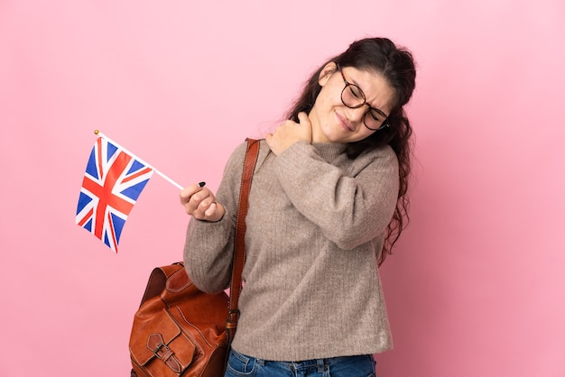 Young russian woman holding an united kingdom flag isolated on pink background suffering from pain in shoulder for having made an effort