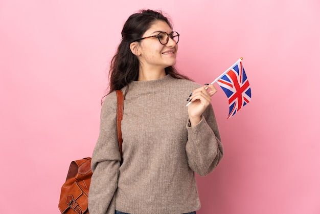 Young russian woman holding an united kingdom flag isolated on pink background thinking an idea while looking up