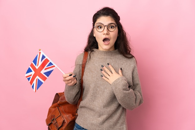 Young russian woman holding an united kingdom flag isolated on pink background with surprise facial expression