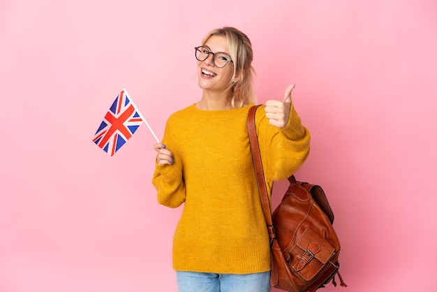 Young russian woman holding an united kingdom flag isolated on pink background with thumbs up because something good has happened