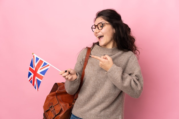 Young russian woman holding an united kingdom flag isolated on pink wall intending to realizes the solution while lifting a finger up