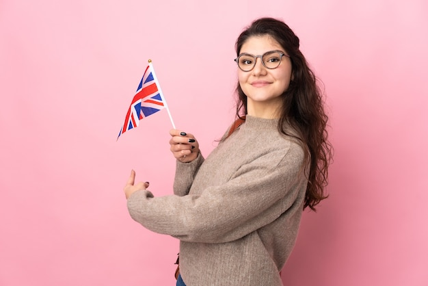 Young russian woman holding an united kingdom flag isolated on pink wall pointing back