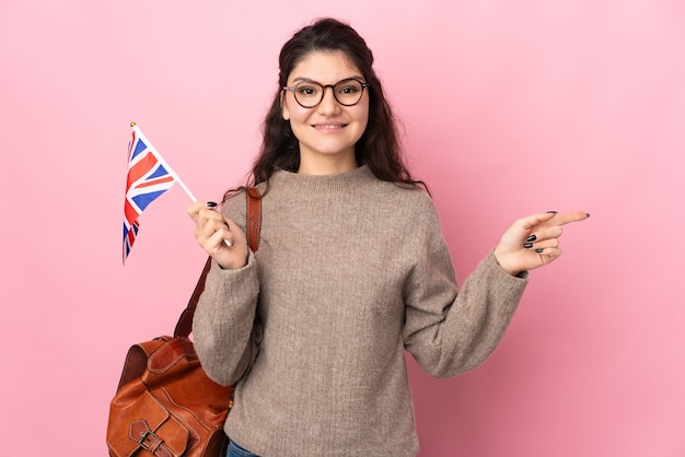 Young russian woman holding an united kingdom flag isolated on pink wall pointing finger to the side