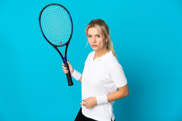 Young russian woman isolated on blue background playing tennis