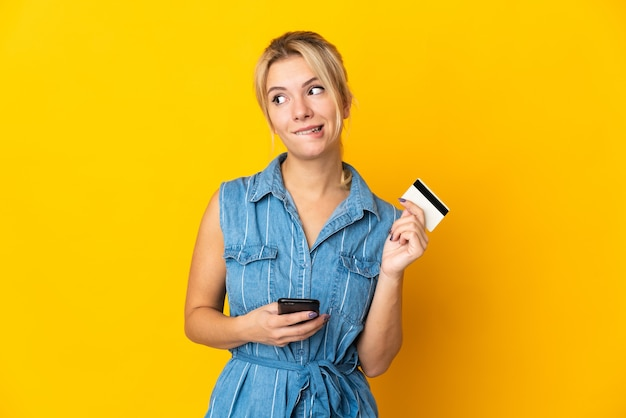 Young russian woman isolated buying with the mobile with a credit card while thinking
