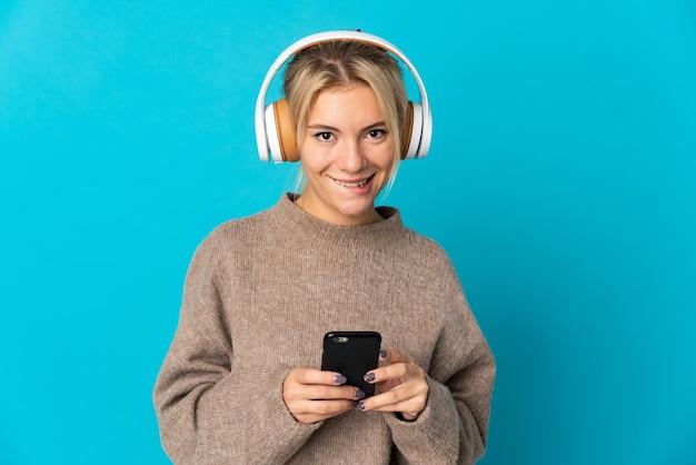 若いロシアの女性は、携帯電話で音楽を聴いて、正面を向いて青い背景で隔離