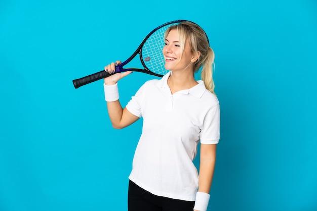 파란색 배경에 고립 된 젊은 러시아 여자 테니스를 치고 올려다