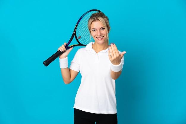 テニスをし、来るジェスチャーをしている青に孤立した若いロシアの女性