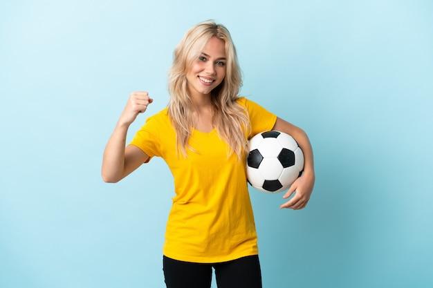 Молодая русская женщина изолирована на синем с футбольным мячом, празднует победу