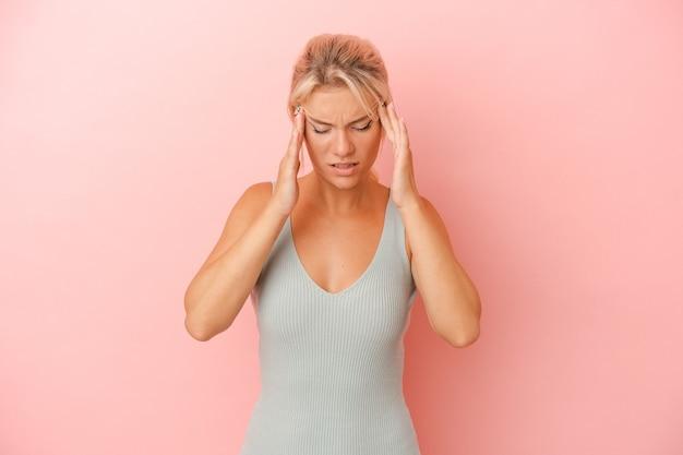 顔の正面に触れて、頭痛を持っているピンクの背景に分離された若いロシア人女性。