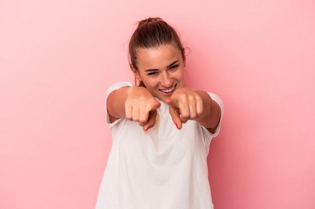 指で正面を指しているピンクの背景に分離された若いロシアの女性。